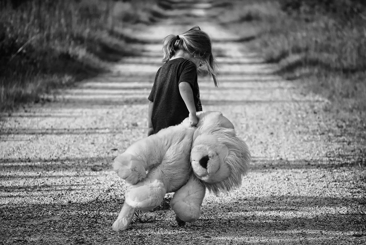 flicka på promenad med stor nallebjörn