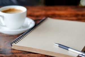 Pen on notebook with coffee.